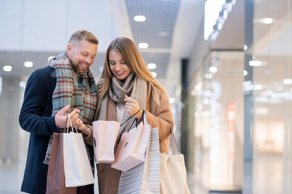 Happy young spouses in coats and scarves looking at what they bought - Stock Photo - Images