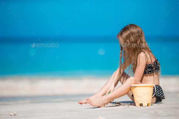 Adorable little girl in swimsuit at tropical beach - Stock Photo - Images
