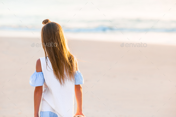 Adorable happy little girl walking on white beach at sunset - Stock Photo - Images
