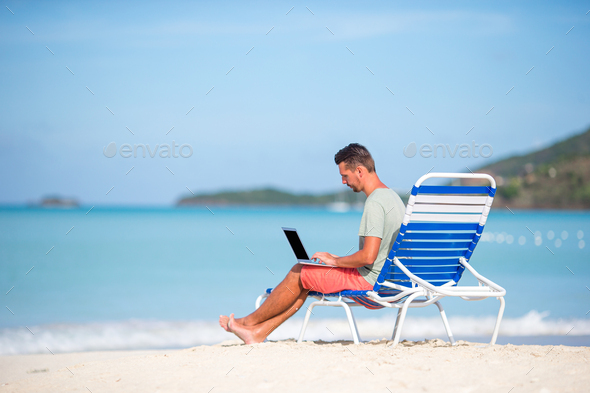 Young man with tablet computer during tropical beach vacation - Stock Photo - Images