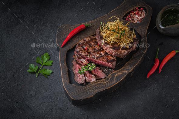 Sliced beef steak on wooden board, dark photo - Stock Photo - Images