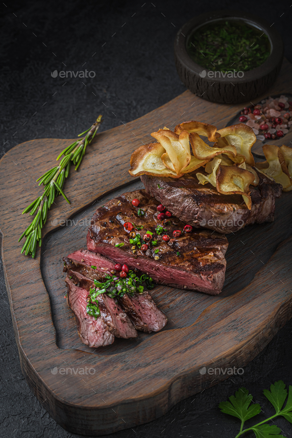 Sliced tenderloin beef steak on wooden board - Stock Photo - Images