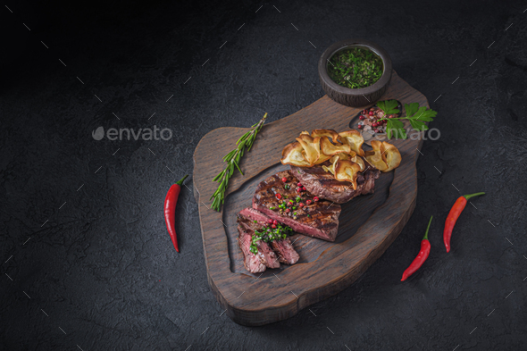 Grilled and sliced beek steak with crispy chips, copy space - Stock Photo - Images
