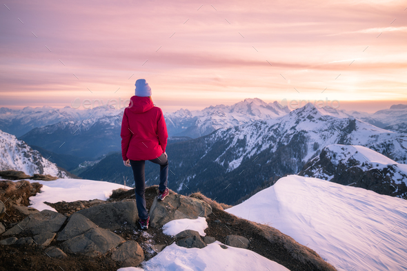 Young woman in snowy mountains at sunset in winter - Stock Photo - Images