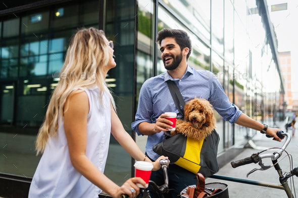 Beautiful couple walking dogs and bicycles outdoors in city - Stock Photo - Images