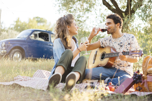 Couple tasting red wine during a picnic in Tuscany - Stock Photo - Images