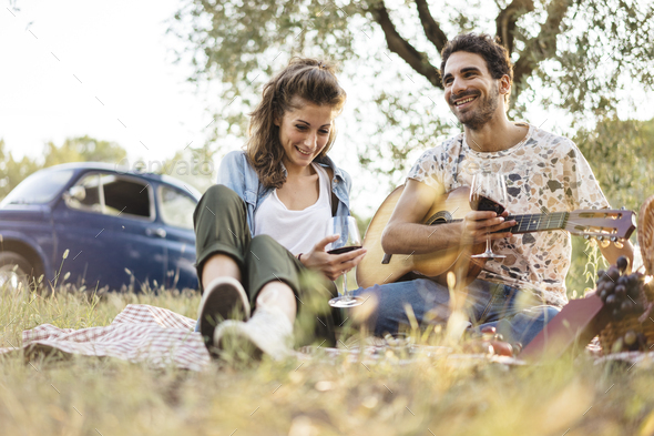 Young man playing guitar during a picnic to his girlfriend - Stock Photo - Images