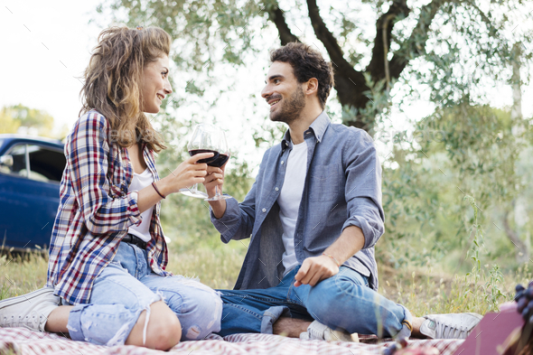 couple tasting wine during a picnic in the countryside - Stock Photo - Images