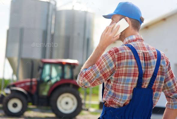 Rear view of farmer talking on the phone - Stock Photo - Images