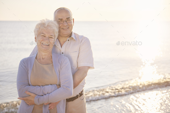 Senior man and woman embracing on the beach - Stock Photo - Images
