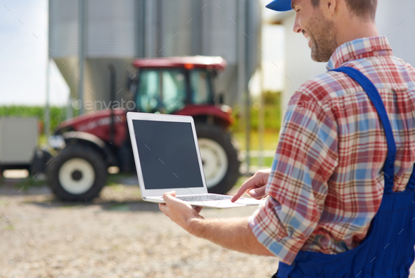 Farmer using laptop on the farm - Stock Photo - Images