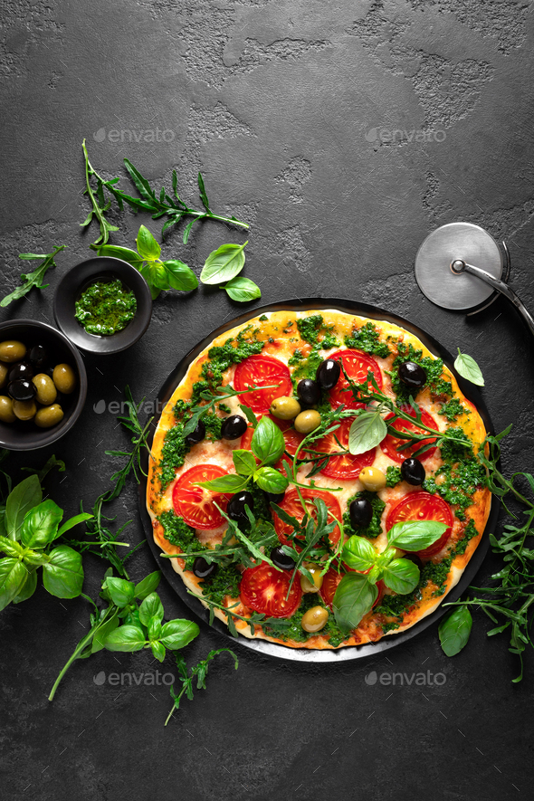 Pizza. Traditional italian pizza with green basil pesto sauce, top view - Stock Photo - Images