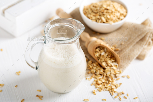 Oat milk. Healthy vegan non-dairy organic drink with flakes - Stock Photo - Images