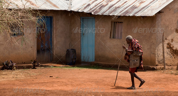 Senior woman walking through village, Tanzania, Africa - Stock Photo - Images