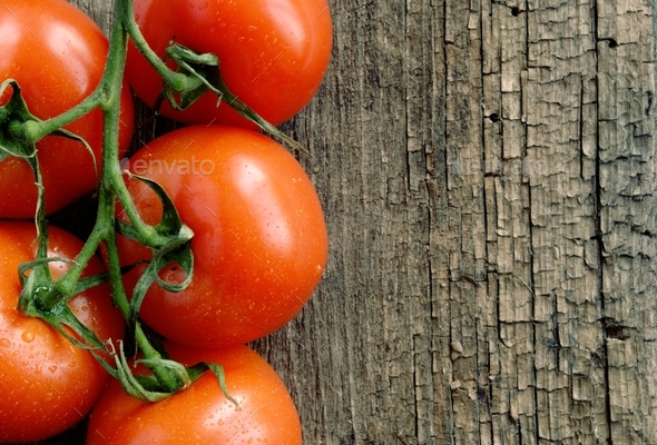 Red tomatoes on the old board - Stock Photo - Images
