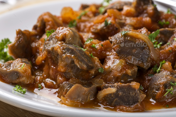 chicken gizzard stew on plate with herbs - Stock Photo - Images