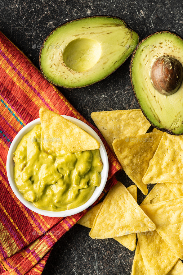 Corn nacho chips and avocado dip. Yellow tortilla chips and guacamole - Stock Photo - Images