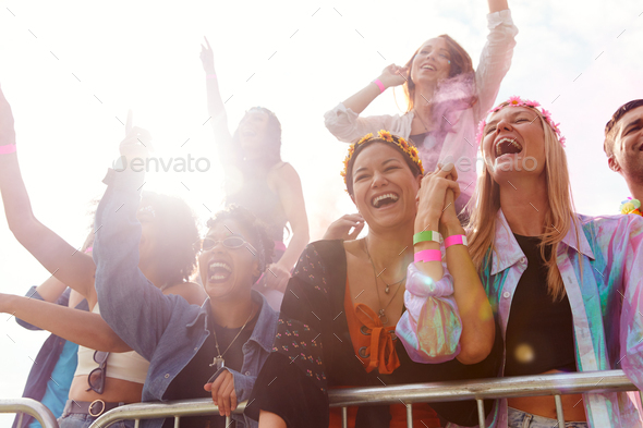 Cheering Young Friends In Audience Behind Barrier At Outdoor Festival Enjoying Music - Stock Photo - Images