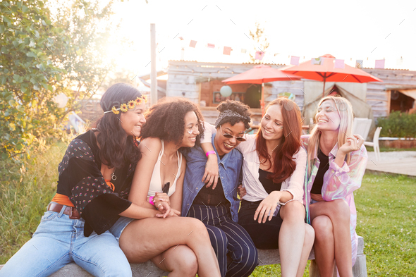 Smiling Female Friends At Music Festival Sitting Outside Together - Stock Photo - Images