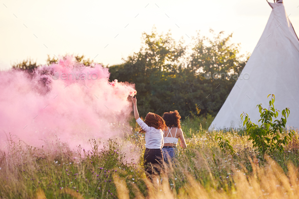 Rear View Of Two Female Friends Camping At Music Festival Running Through Field With Smoke Flare - Stock Photo - Images