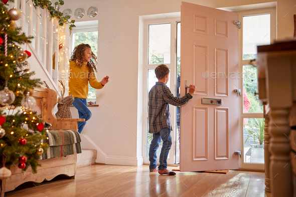 Excited Grandchildren Greeting Grandparents Visiting On Christmas Day - Stock Photo - Images