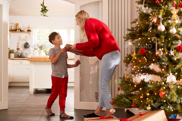 Son Giving Mother Gift On Christmas Morning At Home - Stock Photo - Images