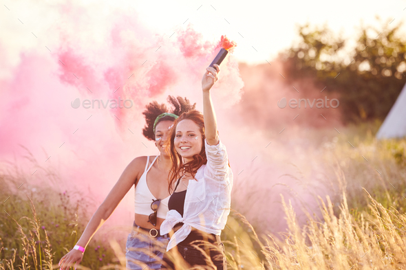 Two Female Friends Camping At Music Festival Running Through Field With Smoke Flare - Stock Photo - Images