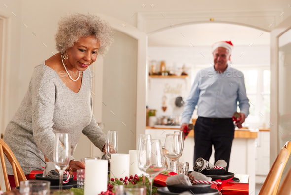 Senior Couple At Home Setting And Decorating Table For Meal On Christmas Day - Stock Photo - Images