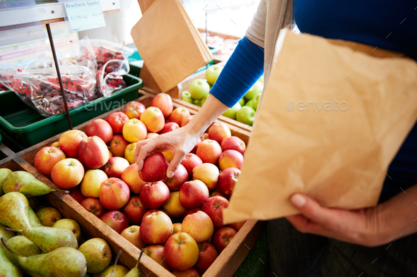 Close Up Of Woman Customer With Paper Bag Buying Fresh Apples In Organic Farm Shop - Stock Photo - Images