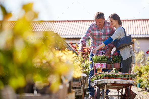 Mature Couple Pushing Trolley With Plants They Have Bought At Garden Center - Stock Photo - Images