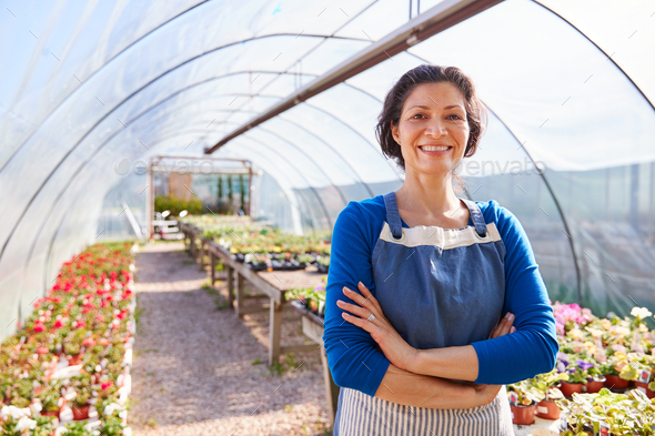 Portrait Of Mature Woman Working In Garden Center Greenhouse - Stock Photo - Images