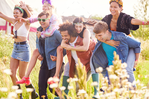 Group Of Friends Walking Back To Tent After Outdoor Music Festival With Men Giving Women Piggybacks - Stock Photo - Images