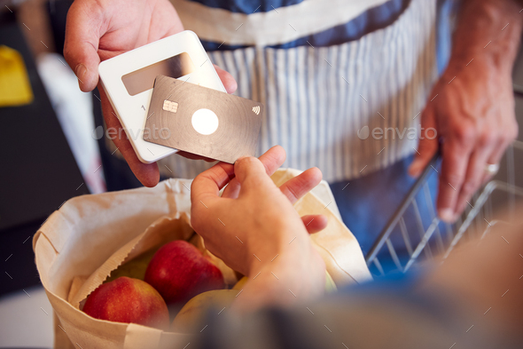 Close Up Of Customer At Checkout Of Organic Farm Shop Making Contactless Payment - Stock Photo - Images