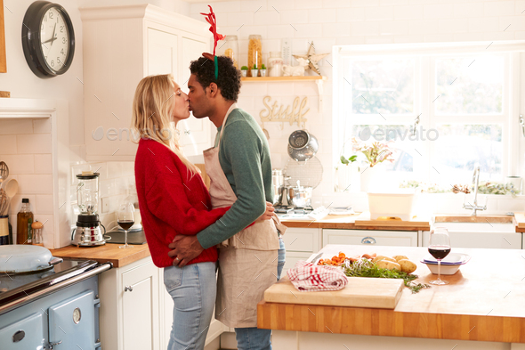 Loving Couple Wearing Fancy Dress Antlers Kissing In Kitchen Whilst Preparing Christmas Dinner - Stock Photo - Images