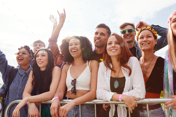 Young Friends In Audience Behind Barrier Dancing And Singing At Outdoor Festival Enjoying Music - Stock Photo - Images