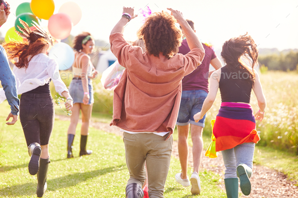 Rear View Of Group Of Friends Walking Back To Tent After Outdoor Music Festival With Balloons - Stock Photo - Images