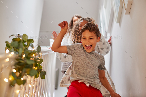 Excited Children Running Downstairs To Open Presents On Christmas Morning - Stock Photo - Images