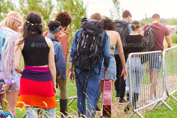 Rear View Of Friends At Entrance To Music Festival Walking Through Security Barriers - Stock Photo - Images