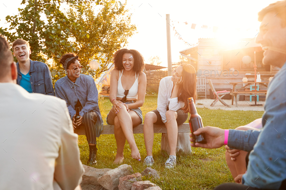 Group Of Young Friends At Music Festival Sitting Outside And Drinking Beer - Stock Photo - Images