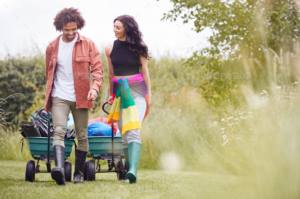 Young Couple Pulling Trolley Filled With Camping Equipment Through Field To Music Festival - Stock Photo - Images