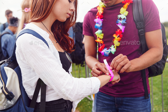 Close Up Of Friends At Entrance To Music Festival Putting On Security Wristbands - Stock Photo - Images