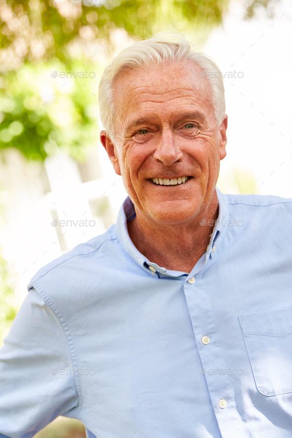 Outdoor Portrait Of Smiling Senior Man In Garden At Home