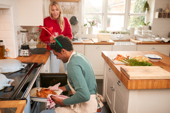 Man Taking Turkey Out Of Oven As Couple Drink Wine And Prepare Dinner On Christmas Day - Stock Photo - Images