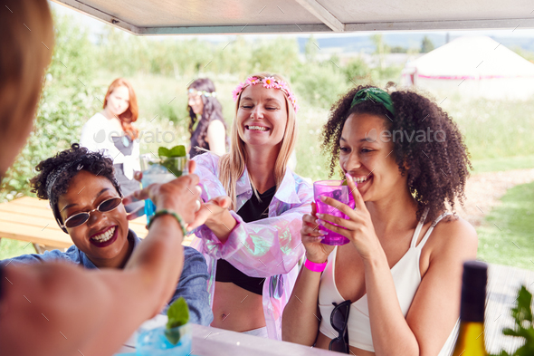 Female Friends Buying Drinks From Bar At Music Festival - Stock Photo - Images