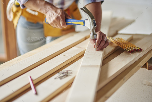 Hammering nails into wooden planks - Stock Photo - Images
