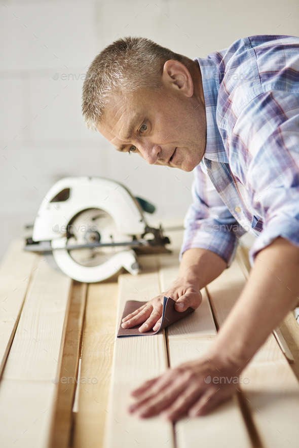 Carpenter used sandpaper for wooden plank - Stock Photo - Images