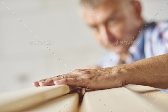 Measuring wooden planks by senior carpenter - Stock Photo - Images