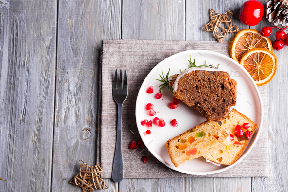 Christmas sliced chocolate cake and fruit cake with white icing and pomegranate kernels on plate - Stock Photo - Images