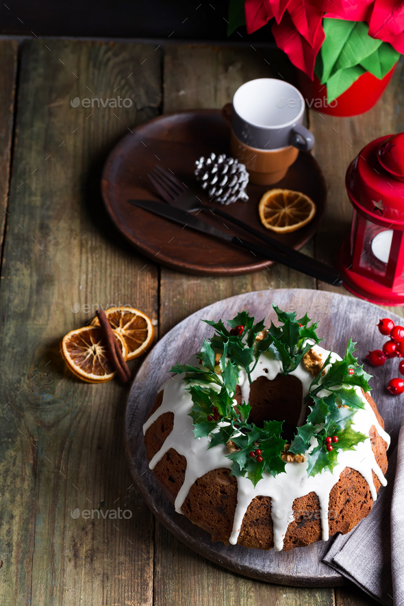 Christmas dark chocolate cake decorated with white icing and holly berry branches with red lantern - Stock Photo - Images