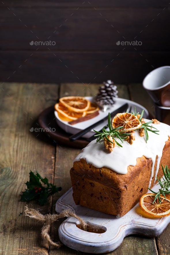 Fruit cake dusted with icing, nuts and dry orange on old wooden background. Christmas and Winter - Stock Photo - Images